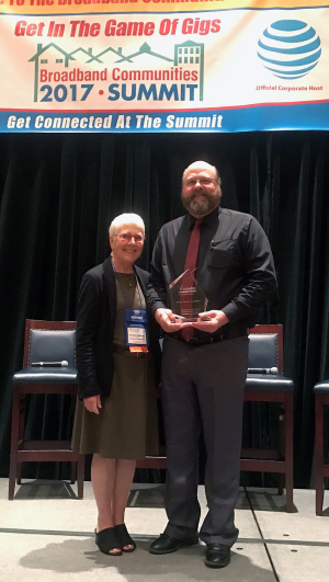 Nate Johnson, Executive VP-Broadband and IT Communications for VCA accepted the Cornerstone Award Wednesday from Barbara DeGarmo, CEO of the Broadband Communities Magazine